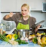 Ragazza felice che cucina alla cucina Fotografia Stock Libera da Diritti