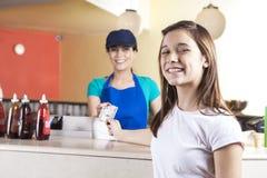 Ragazza felice che dà la nota del dollaro al salone di In Ice Cream della cameriera di bar Fotografia Stock