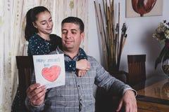 Ragazza felice che distribuisce la cartolina d'auguri al padre sorridente sulla festa del papà immagini stock