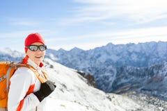 Ragazza felice che fa un'escursione in alte montagne di inverno con lo zaino Fotografie Stock