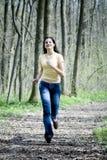 Ragazza felice che funziona nella foresta fotografie stock