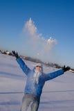 Ragazza felice che getta in su neve Immagini Stock