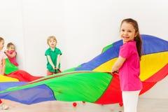 Ragazza felice che gioca con il paracadute variopinto in palestra fotografia stock