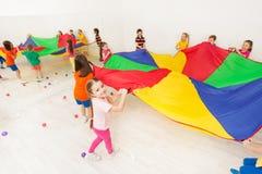 Ragazza felice che gioca il gioco del paracadute con i suoi amici Fotografia Stock Libera da Diritti