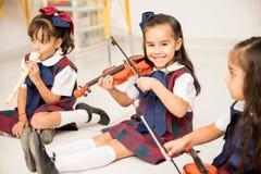 Ragazza felice che gioca il violino in scuola materna Fotografie Stock
