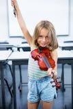 Ragazza felice che gioca violino in aula Immagini Stock