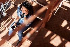 Ragazza felice che gode della canzone sulle scale Fotografie Stock Libere da Diritti
