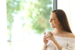 Ragazza felice che guarda attraverso il caffè dell'assaggio della finestra Immagine Stock