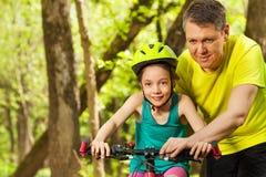 Ragazza felice che impara ciclare con suo padre fotografia stock libera da diritti