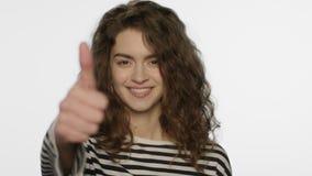 Ragazza felice che mostra i pollici su su fondo bianco Rappresentazione della giovane donna come il segno stock footage