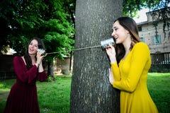 Ragazza felice che parla su un telefono del giocattolo fotografia stock