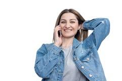 Ragazza felice che parla sullo smartphone isolato su fondo bianco fotografie stock