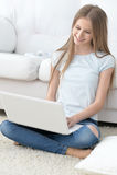 Ragazza felice che per mezzo del computer portatile Fotografia Stock
