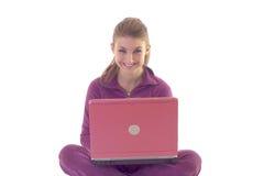 Ragazza felice che per mezzo del computer portatile Fotografie Stock Libere da Diritti