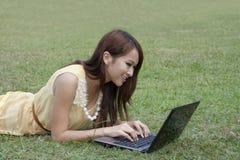 Ragazza felice che per mezzo del computer portatile sul pascolo Immagine Stock
