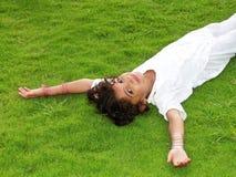 Ragazza felice che pone sull'erba Fotografia Stock Libera da Diritti