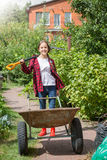 Ragazza felice che posa con la carriola e la pala in giardino a Fotografia Stock