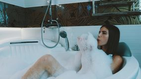 Ragazza felice che prende bagno in pieno di schiuma in bagno Distensione Schiuma del sapone del colpo archivi video