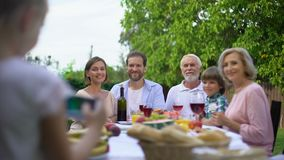 Ragazza felice che prende la foto di famiglia con lo smartphone, cena di celebrazione, memorie stock footage