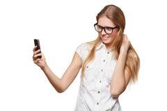 Ragazza felice che prende selfie con il telefono cellulare, in vetri, sopra fondo bianco Immagine Stock