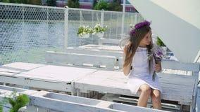 Ragazza felice che riposa ai fiori della barra di baia, di fiuto e sorridere lentamente stock footage