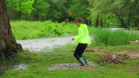 Ragazza felice che salta nella pozza vicino al fiume stock footage