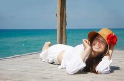 Ragazza felice che si distende sulla priorità bassa del mare Fotografie Stock