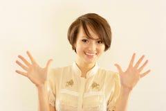 Ragazza felice che si leva in piedi su un beige Fotografia Stock Libera da Diritti