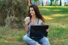 Ragazza felice che si siede con un computer portatile sull'erba e che tiene una tazza di caffè Fotografia Stock