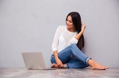 Ragazza felice che si siede sul pavimento con il computer portatile Fotografia Stock Libera da Diritti