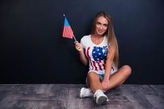 Ragazza felice che si siede sul pavimento con la bandiera di U.S.A. Fotografia Stock Libera da Diritti