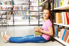 Ragazza felice che si siede sul pavimento vicino allo scaffale per libri Immagini Stock Libere da Diritti