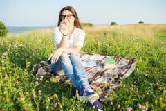 Ragazza felice che si siede sulla coperta all'aperto Fotografia Stock Libera da Diritti