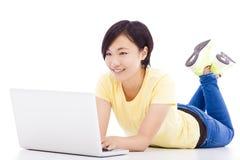 Ragazza felice che si trova sul pavimento con un computer portatile Immagini Stock Libere da Diritti
