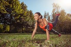 Ragazza felice che solleva gamba in plancia su addestramento Fotografia Stock Libera da Diritti