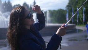 Ragazza felice che sorride alla macchina fotografica che fa selfie alla fontana Movimento lento 1920x1080 HD pieno stock footage