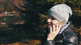 Ragazza felice che sorride e che parla su Smartphone nel parco della città al rallentatore archivi video