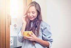 Ragazza felice che sta alla finestra di mattina che beve caffè Fotografia Stock