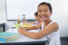 Ragazza felice che studia allo scrittorio dentro in aula Fotografia Stock Libera da Diritti