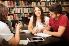 Ragazza felice che studia in una biblioteca Fotografia Stock Libera da Diritti