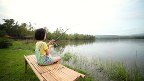 Ragazza felice che tira barretta mentre pescando contro il paesaggio del lago archivi video