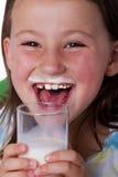 Ragazza felice con i baffi del latte Fotografia Stock