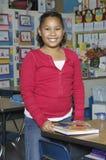 Ragazza felice con il libro in aula Fotografia Stock