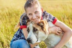 Ragazza felice con il suo pastore centroasiatico del cane nelle zone rurali dentro Fotografie Stock Libere da Diritti