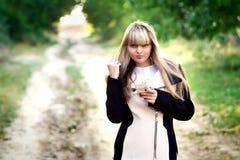 Ragazza felice con il telefono su estate soleggiata Immagini Stock
