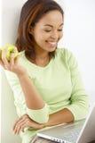 Ragazza felice con la mela ed il computer portatile Fotografia Stock