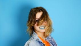 Ragazza felice con la risata lunga dei capelli isolata sopra fondo blu Ritratto di bella ragazza teenager sorpresa e colpita stock footage