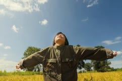 Ragazza felice con le armi alzate nel giacimento verde della molla contro cielo blu Fotografie Stock Libere da Diritti