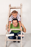 Ragazza felice con suo padre che ridipinge la stanza Immagine Stock