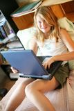 Ragazza felice con un computer portatile Fotografie Stock Libere da Diritti